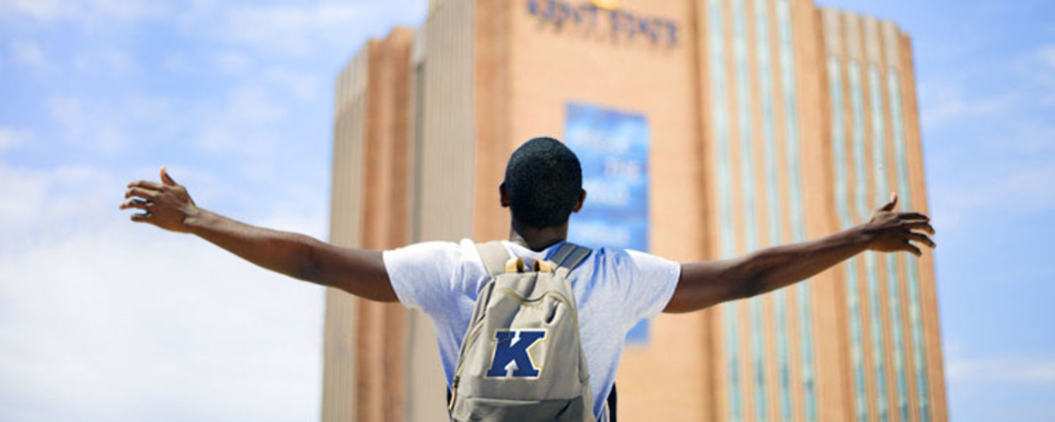 Decision Day May 1: I'm All In. Are You? A student stands with his arms open wide on Kent Campus.