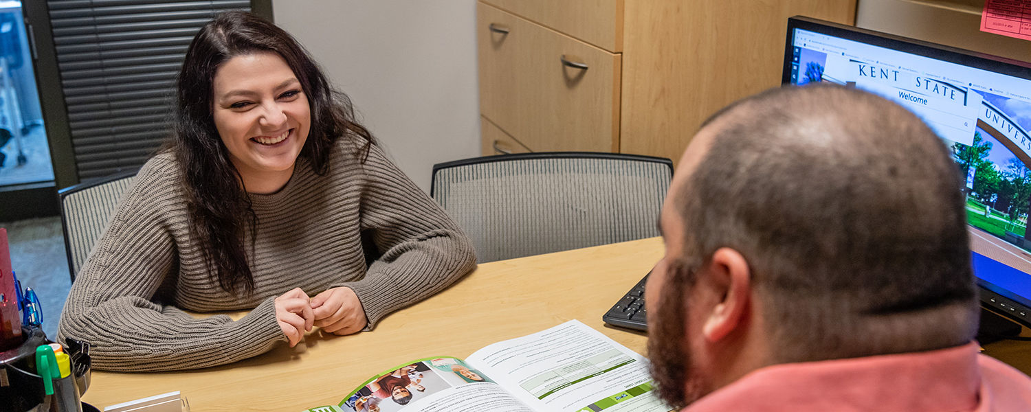 Student sitting with financial counselor in office