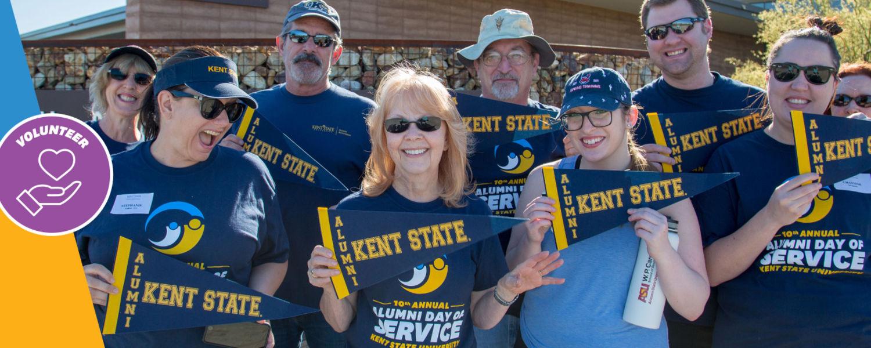 Kent State alumni wearing Kent State t-shirts, holding up Kent State alumni pennant flags
