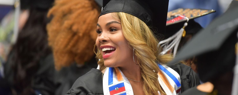 Female student smiling at 2018 Karamu graduation.
