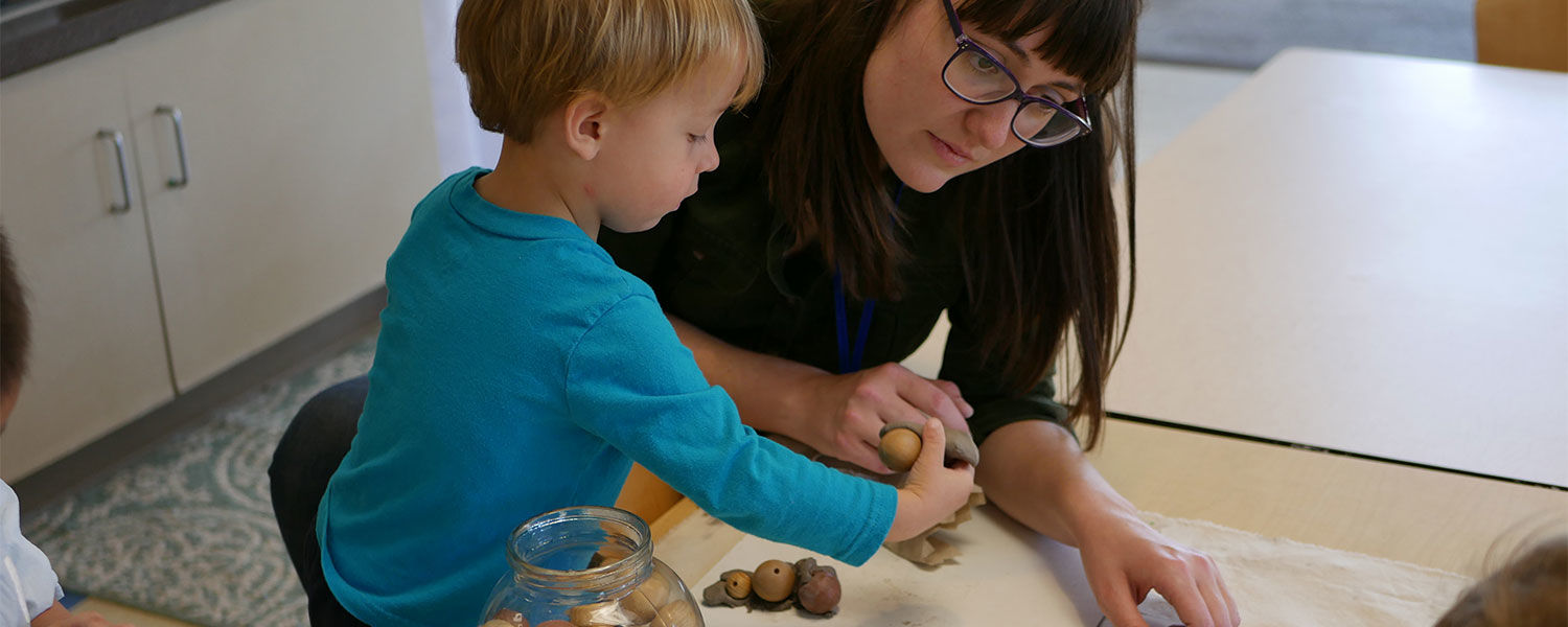 Teacher and child working with beads and clay