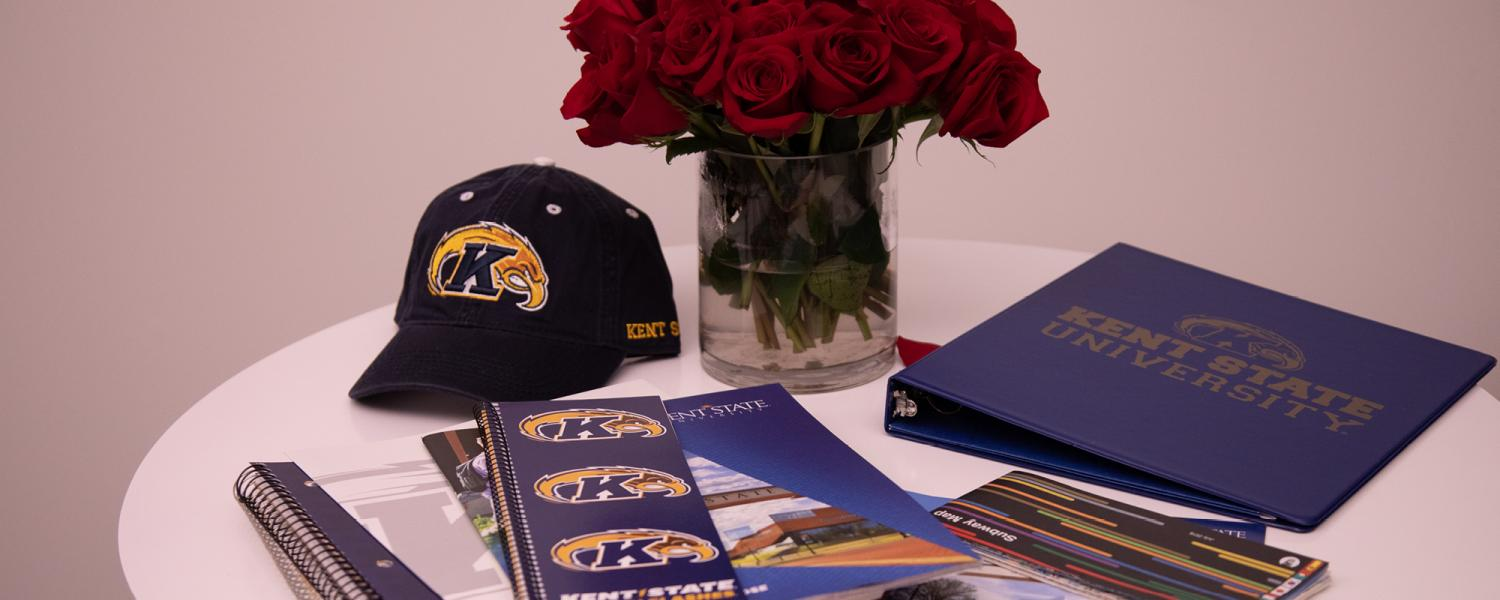 Kent State marketing materials and flowers on a table