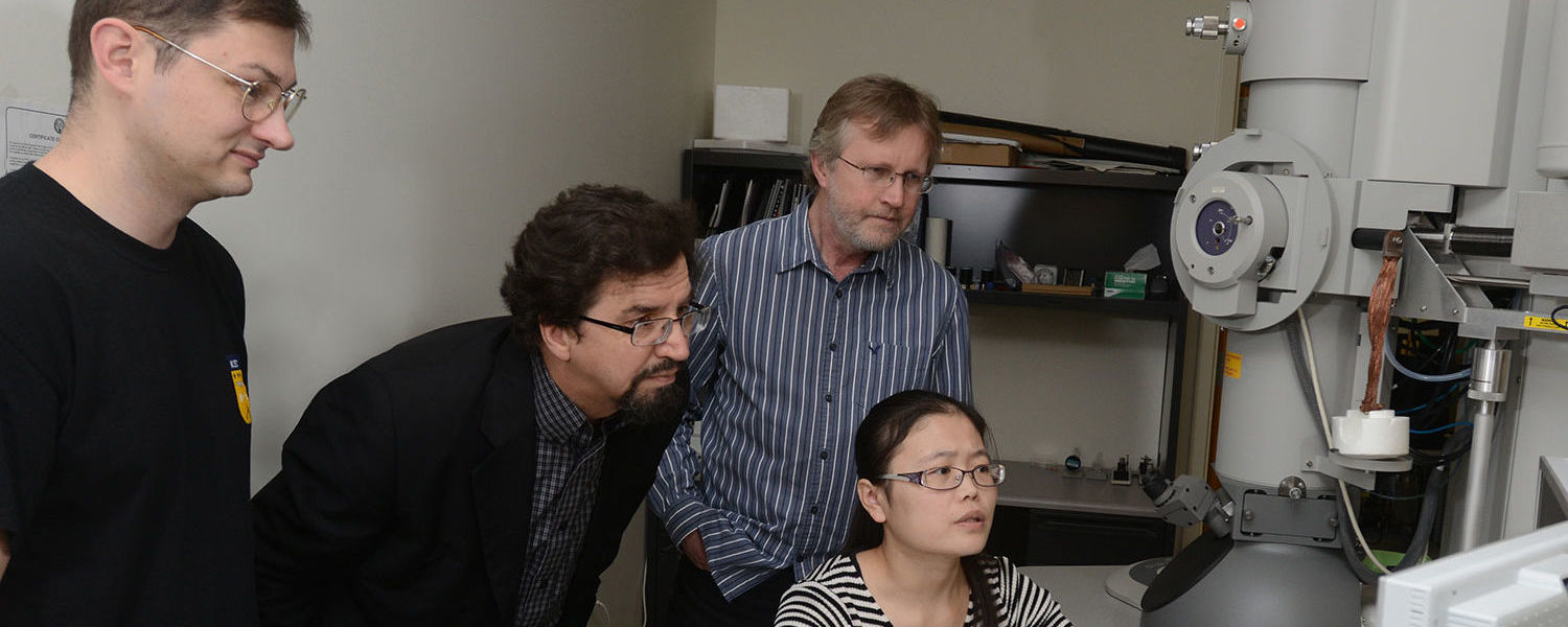 Dr. Oleg Lavrentovich, center, works in a microscopy lab with a colleague and Kent State students