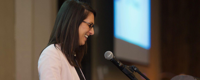 woman presents remarks via podium