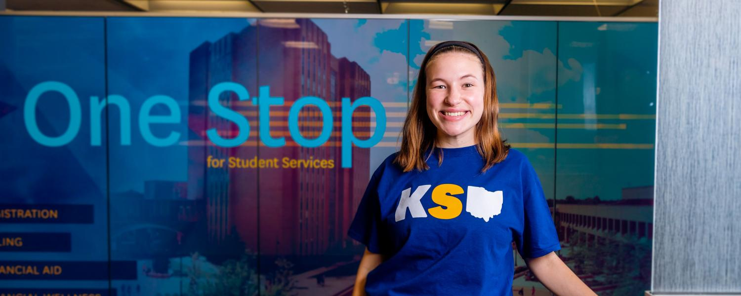A smiling student standing in front of the One Stop sign