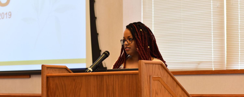 Sage Project female recipient speaks at podium