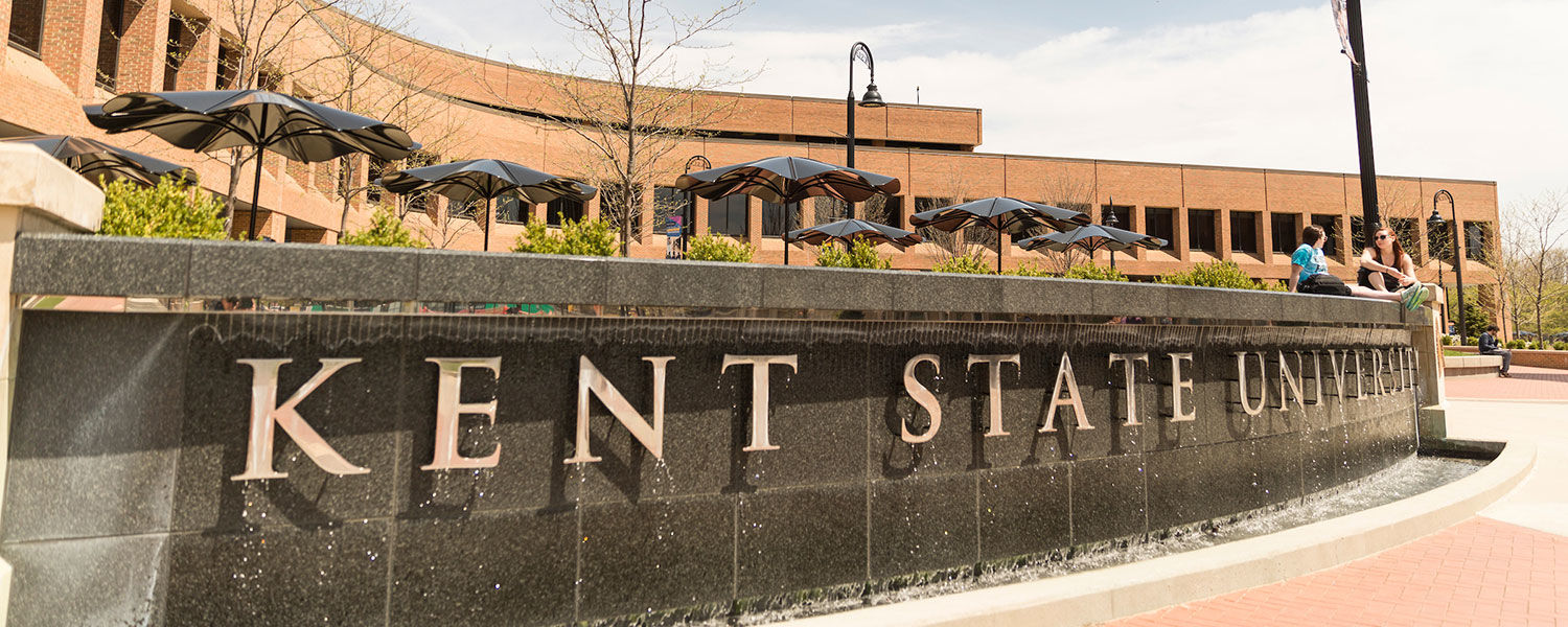 "A waterfall in front of the Kent Student Center with ""Kent State University"" brass letters"