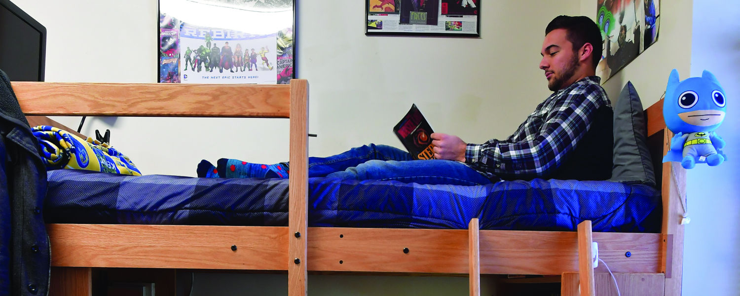 A student reads a book on top of a bunked bed