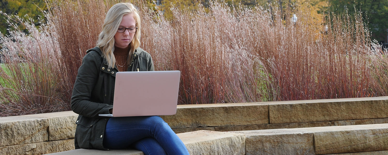 A Kent State student works on an online course outside.