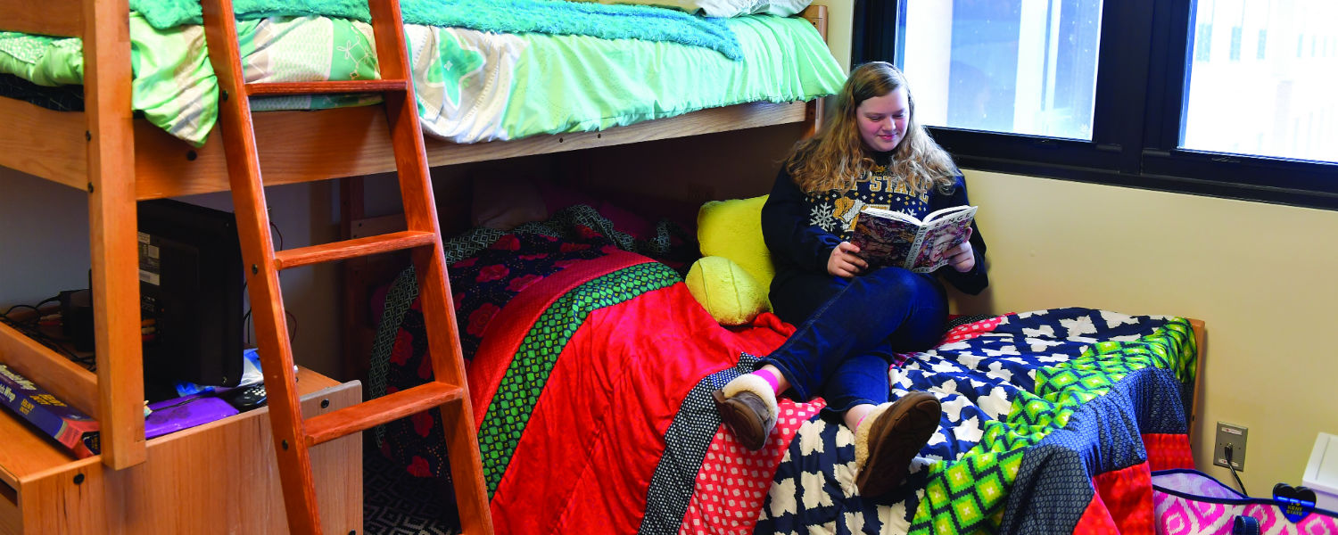 A student reads a book on a bunked bed