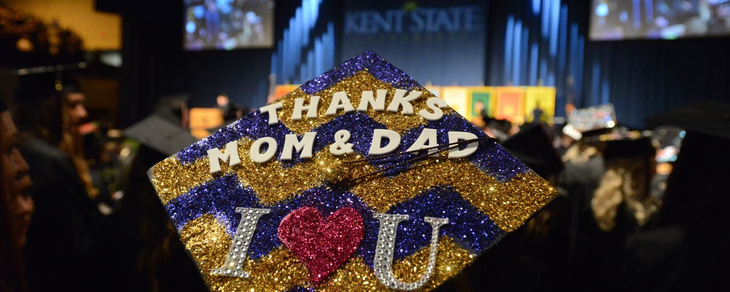 """A Kent State student wears a graduation cap at Commencement, decorated in blue and gold with the words """"Thanks Mom & Dad"""" written across the top."""