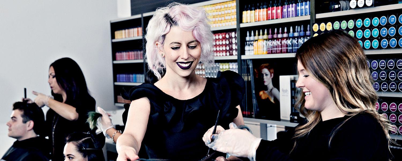 Female stylist helping wash customer's hair