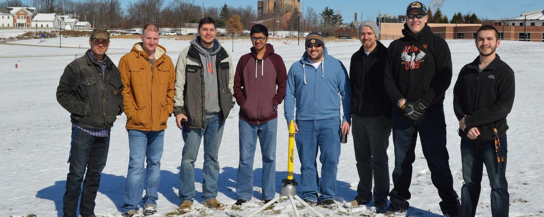 photo High Power Rocket Club team in snowy field with rocket