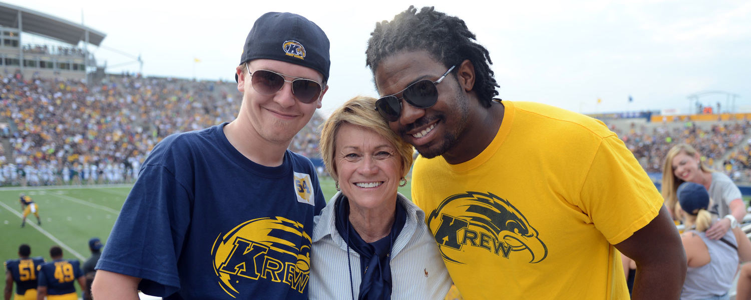 Dr. Beverly Warren takes selfies with students during a home football game at Dix Stadium.