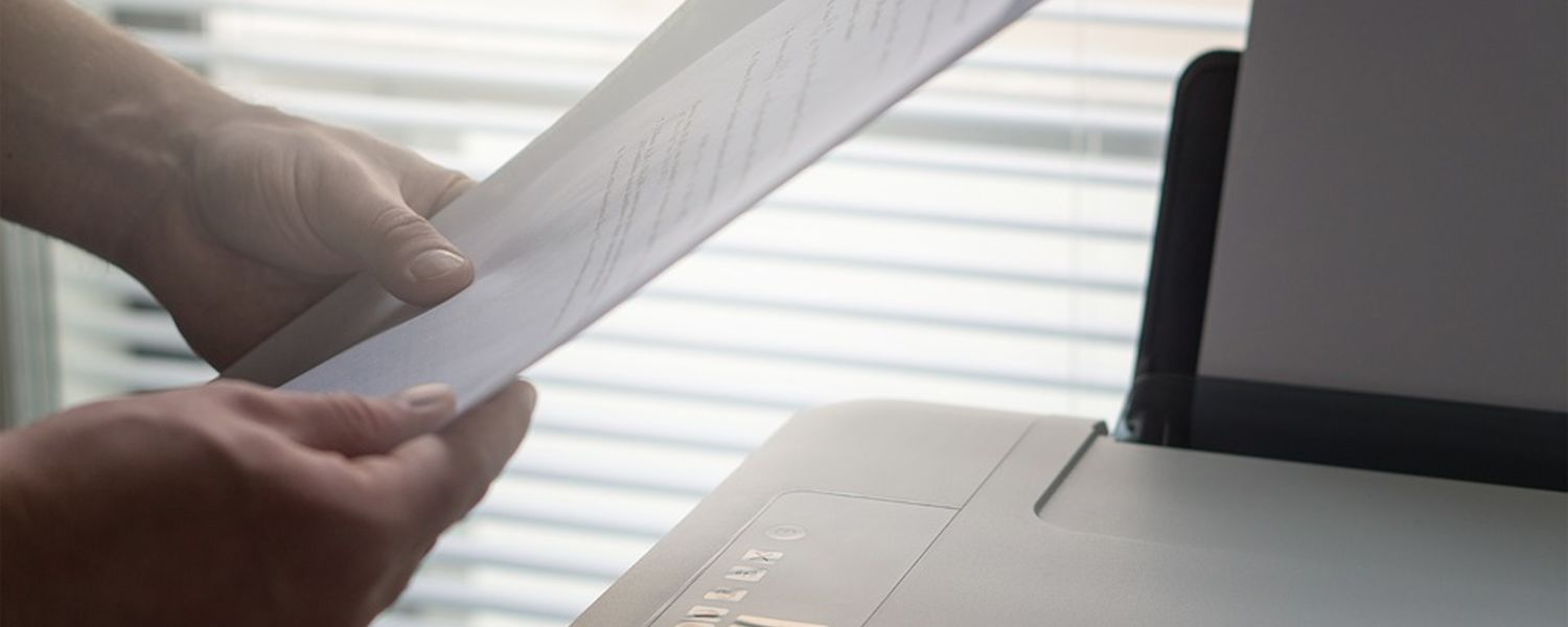 Person holding paper over a printer