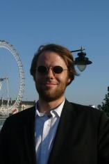 Christian Lengyel standing in front of a ferris wheel