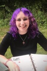 Miranda Linscott smiling, with an open notebook