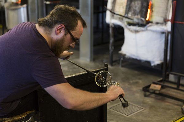 Student works on a glass blowing in CVA
