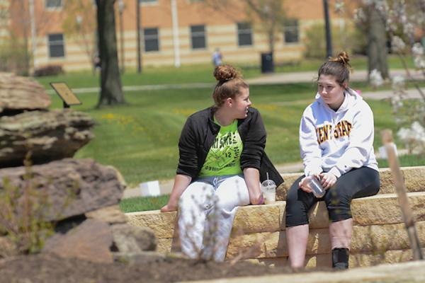 2 students sitting on campus by a fountain, with centennials and eastway center in the background