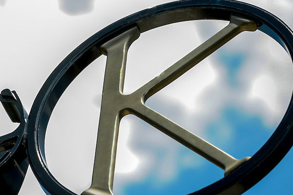 K within a metal circle decorative element with sky in background