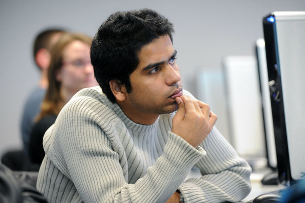A student listens to a class lecture in a computer lab in the Math and Computer Science building.