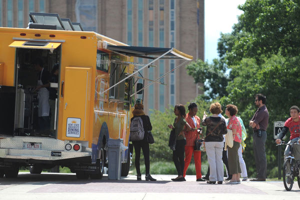 "Students ordering food from ""Fork in the Road"", a food truck, parked on the esplanade."