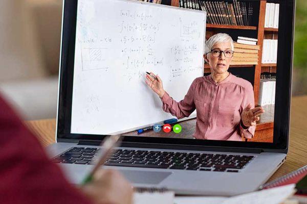 Online Teaching professor on laptop computer teaching student virtually digitally