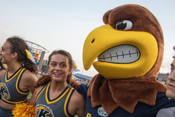 """Kent State's Mascot """"Flash"""" poses with cheerleaders at homecoming"""