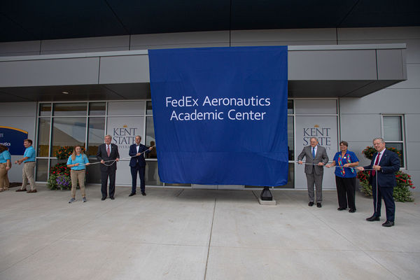 Kent State President Todd Diacon (third from left) is joined by FedEx officials and members of the Kent State community to unveil the new FedEx Aeronautics and Academic Center.
