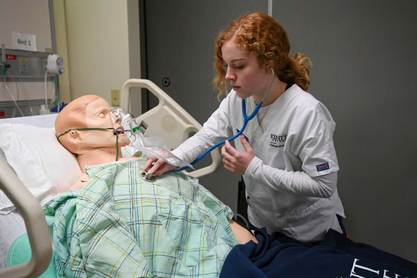 A Kent State University College of Nursing student gets hands-on experience with a patient simulator in the Olga M. Mural Simulation Lab in Henderson Hall.