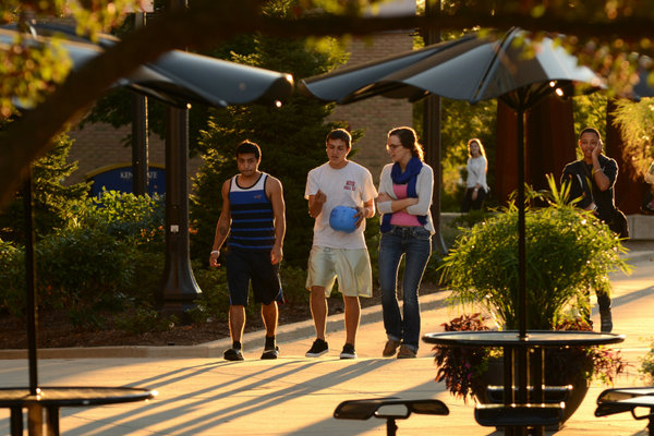 Three students walk through the Risman Plaza on a warm fall evening.