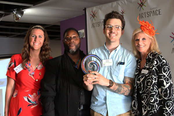 Dillon Sedar receives the Arts Alive Arts Educator Award from Summit Artspace.  He holds the award surrounded by Summit Artspace employees.  Arts Alive logo is on the right.