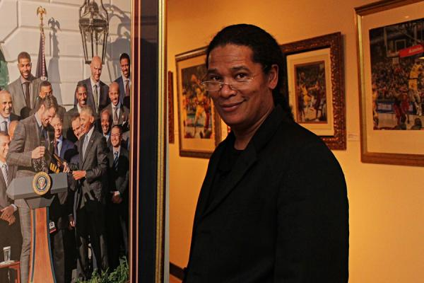 Georgio Sabino III at his exhibition of photography standing in front of a photograph of President Barack Obama.