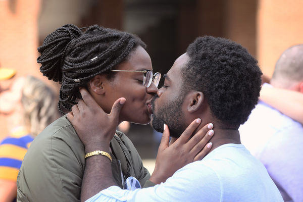 Kent State graduates Lakysha Robinson, '17, and Venix Cador, '15, share a kiss during the Alumni Association's Kiss on the K tradition on Risman Plaza during 2018 Homecoming.