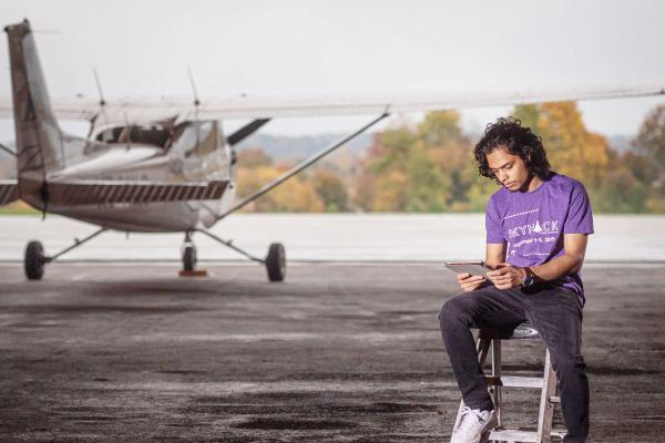Saroj Dahal sitting on a ladder with a tablet.