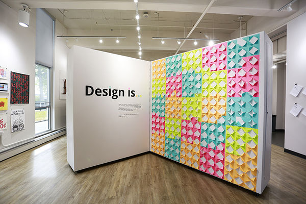 "Display of the sign for the ""Design is"" graduate student show"