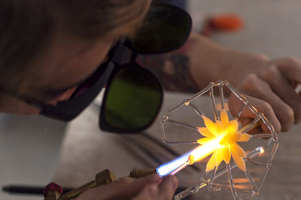 Flameworking glass, student works on a glass flower