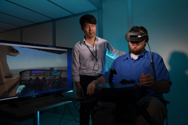 photo Dr. Oh and student demonstrate Dr. Oh's flight simulator