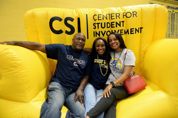 Kent State student and her family take a photo on an inflatable couch.