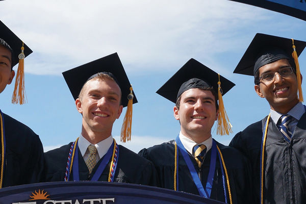 Group of Kent State alumni in graduation regalia, on commencement day