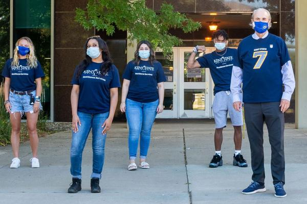 Photo of Kent State President Todd Diacon and students socially distanced and wearing masks in Kent State gear