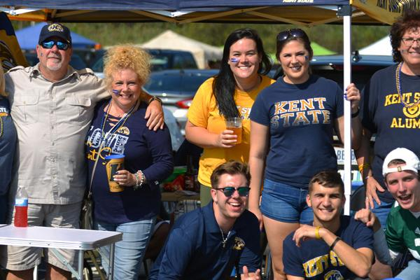 Photo of individuals, gathered together, wearing Kent State clothing and posed and smiling for the camera