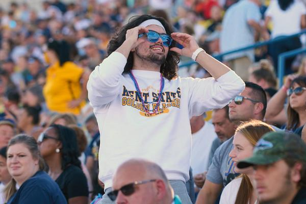 Photo of student wearing sunglasses at homecoming football game