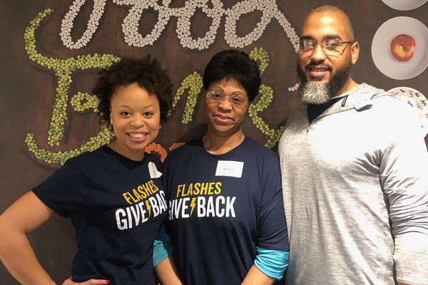 Alumni wearing Flashes Give Back tshirts, smiling, participating at a local Food Bank