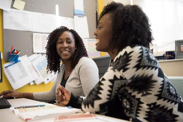 Image of two women talking over paper work.