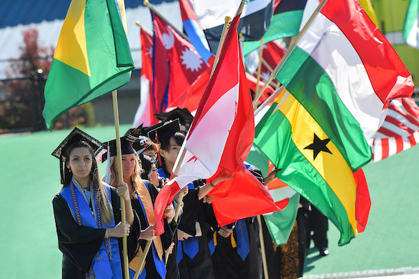 Students holding flags of different nations at commencement.