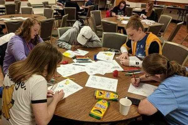 Kent state students work on a service activity around a table.