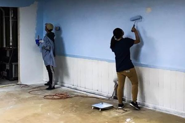 Students paint walls during a day of service