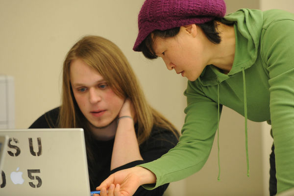 Hyangsook Lee, an assistant professor in the School of Journalism and Mass Communication, helps a student with a multi-media presentation in a classroom in Franklin Hall.