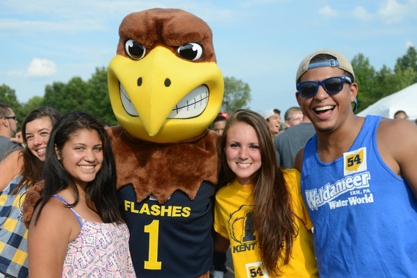 Students gather around Flash for a group photo at a home football game